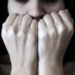 A woman cover her face with her fists in a very anxious moment