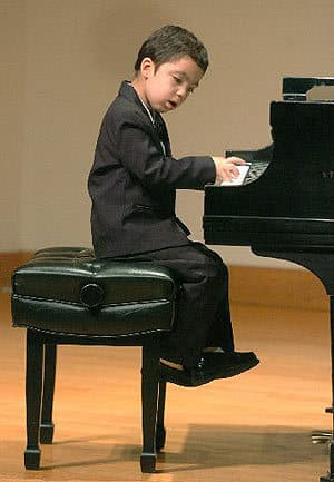 A small boy playing piano